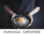 hands holding black bowl with... | Shutterstock . vector #1289225206