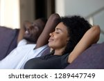 Relaxed african couple enjoying peaceful rest breathing fresh air at home on comfortable couch, happy lazy young black couple having nap leaning on sofa relaxing in living room feel no stress free - stock photo