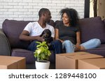 Stock photo young african american couple happy to move into new home with pet and boxes black family tenants 1289448100