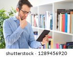man holding ebook on bookshelf... | Shutterstock . vector #1289456920