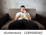 Stock photo the guy in the shirt is lying on the couch eating chips and watching a sports channel the concept 1289608360