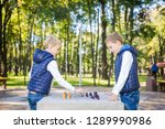Small photo of The topic is children learning, logical development, mind math, miscalculation moves advance. Big family two brothers Caucasian boys playing chess in the park in bright sunny weather in the autumn.