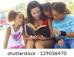 teenage girl reads to her three ... | Shutterstock . vector #129036470