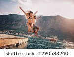 young couple jumping from a... | Shutterstock . vector #1290583240