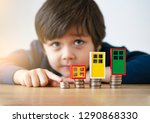 Blurry face of child playing with the row stacks of British coins with plastic door frame and window frame on wooden table. Learning financial responsibility and planning savings concept.