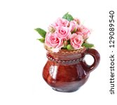 Bunch of pink garden roses in a jug on a white background. - stock photo