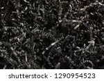 Small photo of Close up of crinkled shredded black paper box filler for shipping fragile items to prevent damage and breakage