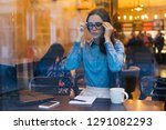 a girl in glasses sits at a...   Shutterstock . vector #1291082293