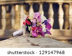 A beautiful wedding bouquet lying on a stone over old house background. Vintage style. Outdoor shot. - stock photo