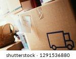 "Small photo of Move. Cardboard, boxes and stuff for moving into a new home, Text: ""Geschirr & Dirndlkleider, Schmuck, Gutscheine"""