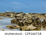 boat behind a Reef on a Brazilian Beach - stock photo