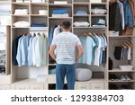 man choosing outfit from large... | Shutterstock . vector #1293384703