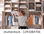 Small photo of Woman choosing outfit from large wardrobe closet with stylish clothes and home stuff
