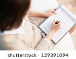 female counselor writing down... | Shutterstock . vector #129391094
