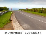 Empty road to the ocean with two signs, San Miguel, Azores, Portugal - stock photo
