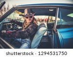 Cowboy in the Car. Caucasian Men Wearing Western Style Hat in His Classic Vehicle. American West Concept. - stock photo
