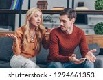 Small photo of emotional upset couple sitting on couch and quarreling about smartphone, mistrust concept