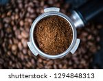 Bottomless filter with grind beans on a wooden black table. Roasted coffee beans. Espresso coffee extraction. Prepare of espresso. - stock photo