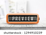 Preview sign in form of a retro alarm clock on a wooden desk in a bright room with sunlight