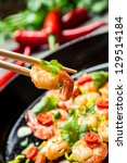 Closeup of tasting shrimp with herbs on chopsticks - stock photo