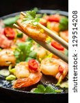 Closeup of sauteed shrimp on chopsticks - stock photo