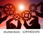 gears in the hands of people on ... | Shutterstock . vector #1295403193