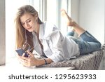 young beautiful woman listens... | Shutterstock . vector #1295623933