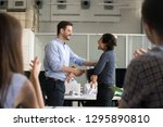 diverse colleagues shaking... | Shutterstock . vector #1295890810