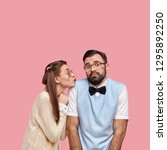 Small photo of Shot of attractive woman in old style clothes, gives kiss to clumsy boyfriend expresses love and care pose together against pink background. Bearded man feels awkward during first date with girlfriend