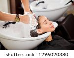 beautiful brunette washes hair... | Shutterstock . vector #1296020380