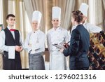 Small photo of restaurant manager and his staff in kitchen. interacting to head chef in commercial kitchen.