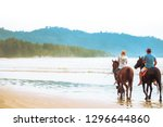 Stock photo tourist couple is enjoying riding horses on the beach with beautiful view in thailand people 1296644860