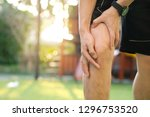 knee pain .man stand at park ... | Shutterstock . vector #1296753520