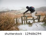 Walker Climbs A Stile In The...