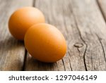 two eggs on weathered wooden... | Shutterstock . vector #1297046149