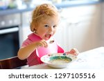 adorable baby girl eating from... | Shutterstock . vector #1297105516