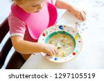 close up baby girl eating from... | Shutterstock . vector #1297105519