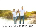 a happy family walks along the... | Shutterstock . vector #1297131406