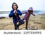 twin girls standing on remains... | Shutterstock . vector #1297334593