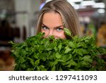girl chooses parsley in the... | Shutterstock . vector #1297411093