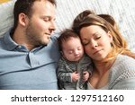 a beautiful couple with newborn ... | Shutterstock . vector #1297512160
