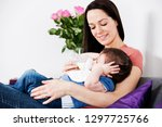 mother at home feeding her baby ... | Shutterstock . vector #1297725766