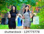 two happy laughing women after shopping - stock photo