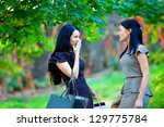 two beautiful women talking in colorful park - stock photo