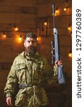 Small photo of Gamekeeper concept. Man with beard wears camouflage clothing in wooden interior background. Macho on strict face at gamekeepers house. Hunter, brutal hipster with gun in his hand ready for hunting.