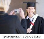 smiling female graduate posing... | Shutterstock . vector #1297774150
