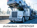 Small photo of Big rig car hauler professional bonnet powerful semi truck transporting cars on two levels industrial semi trailer driving on winter frosty road with frost grass and trees on roadside