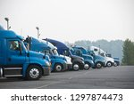 Small photo of Profiles of different big rig long haul semi trucks with high cab standing on parking lot waiting for loading and possibility of continuing to the destination according to approved schedule