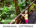 little girl hiking in jungle.... | Shutterstock . vector #1297900663