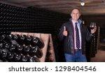 male winemaker giving tour... | Shutterstock . vector #1298404546